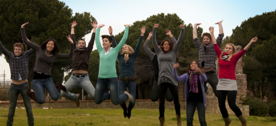 line of young people in a field jumping into the air